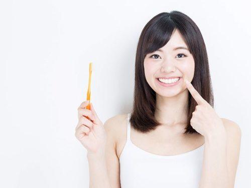 オレンジの歯ブラシを持つ女性